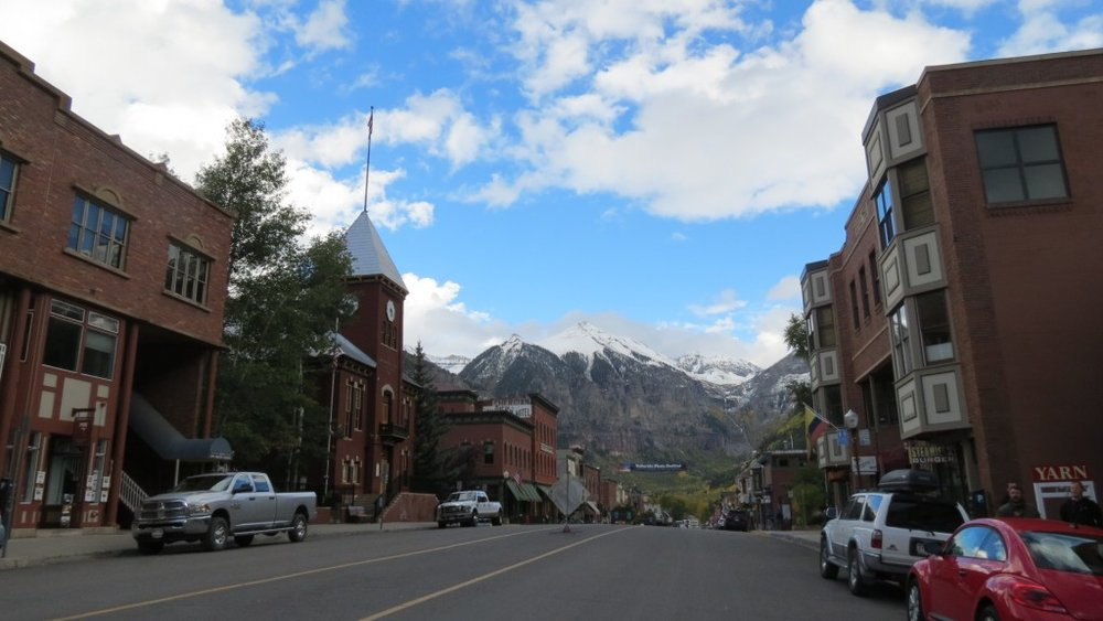 Downtown Telluride with a free stuff wall, lattes at the Steaming Bean, PO boxes only, the occasional wild black bear, a gondola from the street to the mountain and hitching posts for your dog.