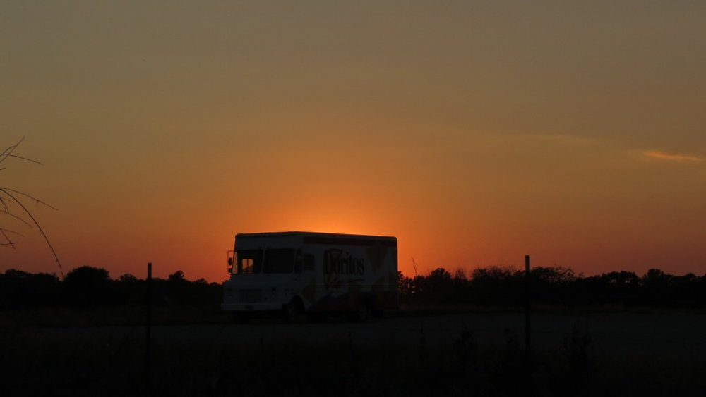 """An empty dorito truck faces the swollen peach sunset. """"Alone again,"""" it sighs, and nods to the bleating twilight bugs, waiting for the light to fade to black."""