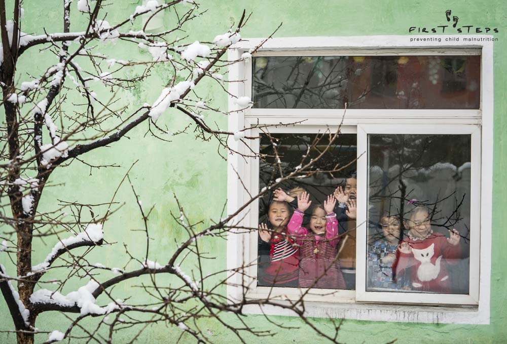 - Children look through the window at the Yangji Daycare in Wonsan