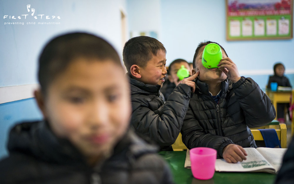 The students are wearing their jackets in the classroom because the rooms are unheated, another consequence of ongoing sanctions. None of this stops the children from having some fun with each other!