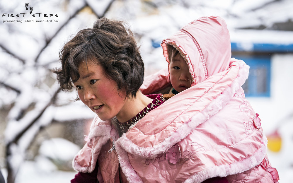 A mother and her son arriving to the Yangji Daycare in Wonsan, Kangwon Province