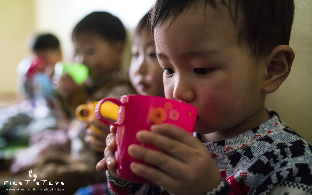 Careful sips of warm nutritious soymilk at the Yangji Daycare