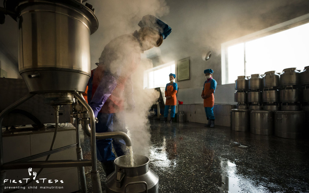 The Nampo Foodstuff Factory uses energy-efficient First Steps' VitaCows to make the soymilk each day. The VitaCow is powered by electricity and can produce 40 -45 litres of soymilk per hour. In this photo the cooked soymilk pours into a stainless-steel milkcan.