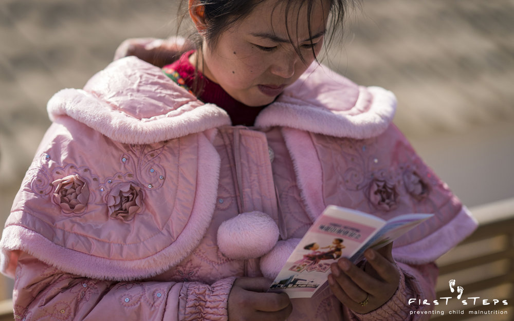 Choe Yun-Mi reads an informational brochure on micronutrient Sprinkles at the Shinmi Clinic.