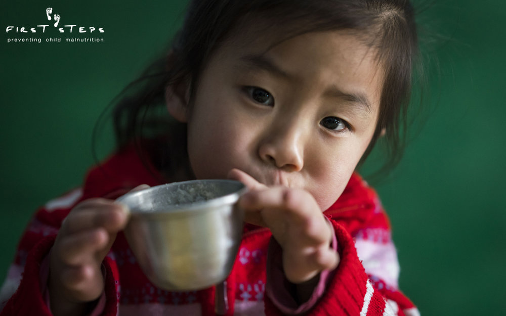 Due to a lack of electricity, the workers at the Sopo #2 Mobom Daycare must grind soybeans by hand to make the soymilk for the children