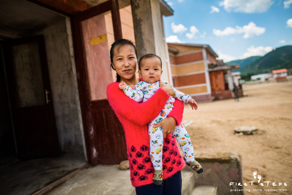 Mun Kum Hae and her six-month old son Kim Whi-Bok stand outside their new home which was built after the flood.