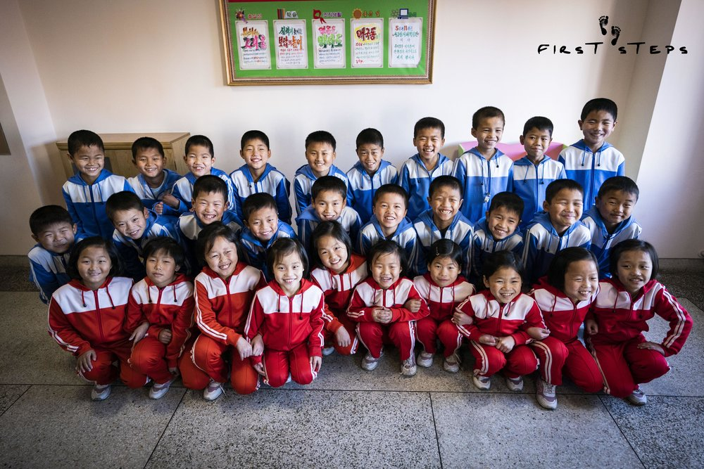 A class of nine-year-old students at the Wonsan Primary Boarding School (orphanage) are all smiles as they get ready for an outdoor exercise session.