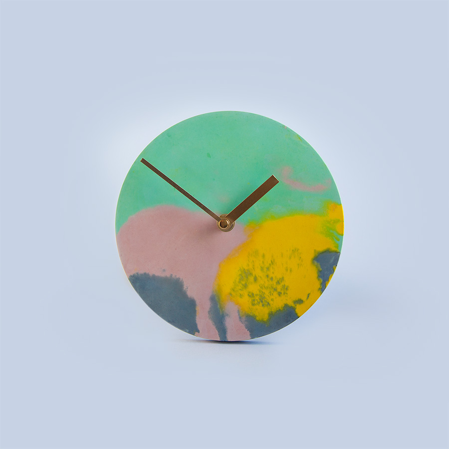 Round Concrete Clock   Contemporary concrete clock with vibrant palette.  Dimensions: 18cm diameter Hangs by the clock mechanism on the back - 1.5cm out from the wall.  £60