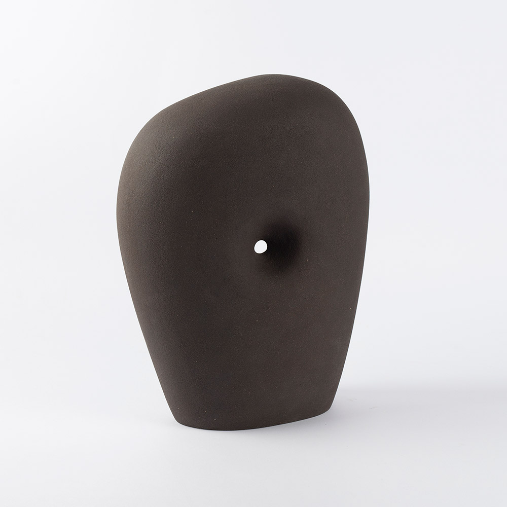 'Variations on a form: Wormhole'  Ceramic: Black Stoneware  29cm (h) x 24cm (w) x 15cm (d)  £445  A wormhole is a theoretical passage through space-time that could create shortcuts for long journeys across the universe. Wormholes are predicted by the theory of general relativity.  The form of this piece in particular (and the basic 'monolith' form for this series as a whole) is a nod to one of my favourite artists, Barbara Hepworth.