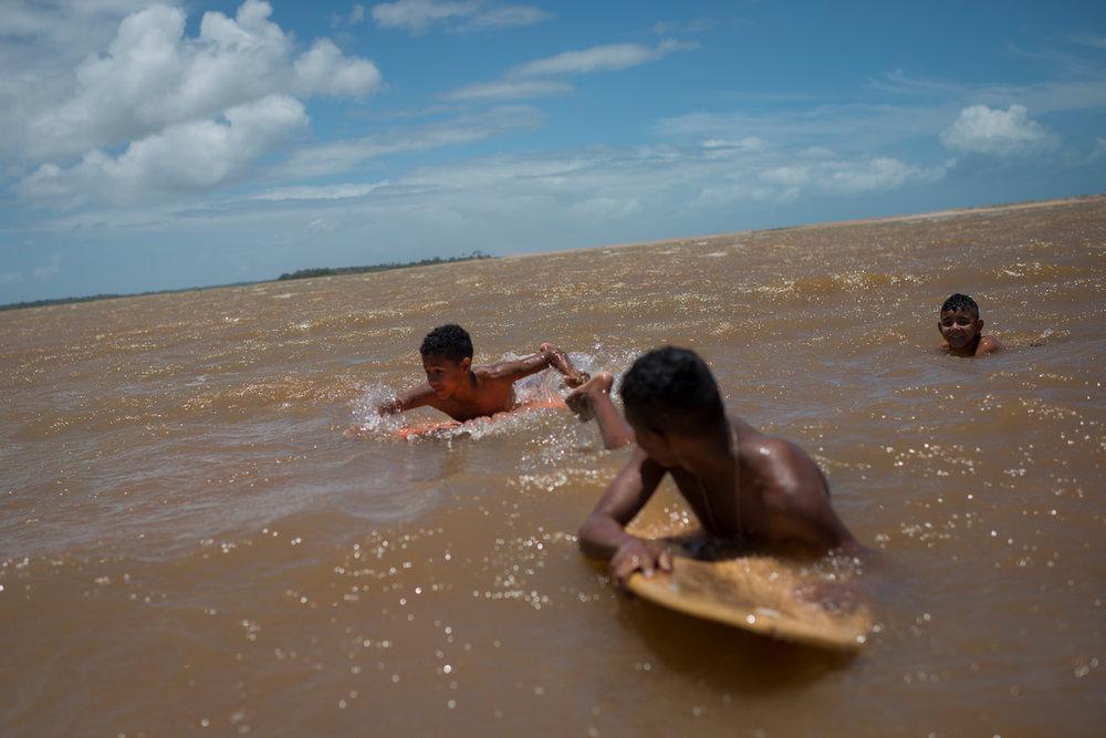 Nov. 18, 2017. Crianças se divertem na manhã de um sábado com pequenas ondulações na margem da boca do rio Doce,arriscando o contato da pele com as águas com rejeitos de ferro, chumbo, arsênio e mercúrio que vieram de Mariana, Minas Gerais -- e aniquilaram os 800 km de vida do rio Doce,depois que a barragem de rejeitos de minério da mineradora Samarco S.A. rompeu, em 5 de novembro de 2015, no distrito de Bento Rodrigues.