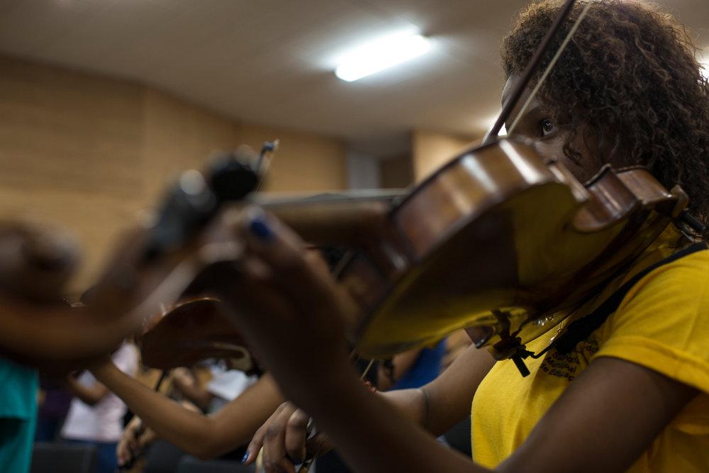"""Dez. 5, 2017. Os instrumentos que pertencem ao projeto foram doados em diferentes gestões da prefeitura, além dos que chegaram através de doações da sociedade. Os principais pontos que Sarah desenvolve durante os ensaios da orquestra (foto) e nas aulas de música são a disciplina, a responsabilidade e o bom desempenho musical. Rígida e perfeccionista à frente das orquestras e coros, ela também educa os jovens, além de ensiná-los a técnica musical. O aluno Gabriel Martins, 10 anos de idade e há 3 no projeto, diz que """"sem a professora Sarah seria tudo desorganizado""""."""