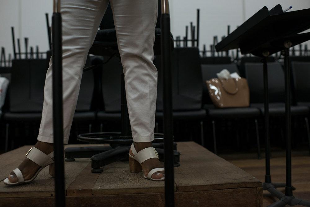 """Dez. 5, 2017. Durante o ensaio da Banda de Concerto (cordas, metais e sopros) na sede do projeto, é possível observar a vaidade da maestrina. Está sempre arrumada, com unhas pintadas, batom, cabelos cuidados, sapatos com salto e acessórios que condizem com seu estilo feminino. """"Se na África os negros eram reis e rainhas, eu sou uma rainha!"""", brinca Sarah, nome que vem do hebraico e significa princesa."""