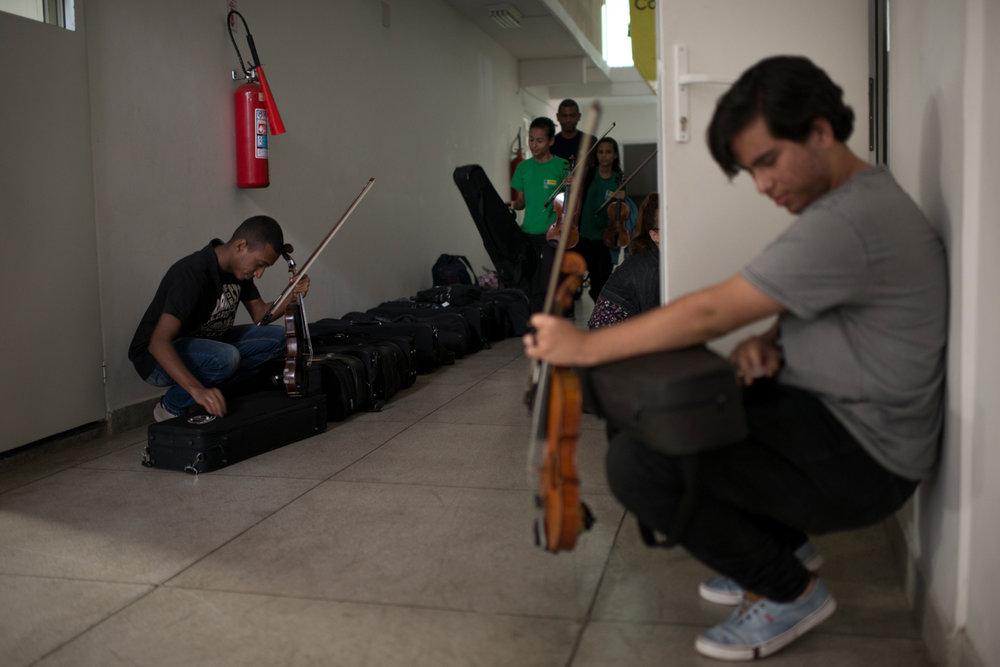 Dez. 5, 2017. Ao fim do ensaio de três horas, os alunos guardam os instrumentos do projeto em cases que ficam organizados no chão do lado de fora da Sala de Ensaio. Felipe Silva, 17 anos (à direita na foto), é considerado um aluno promissor: em janeiro de 2017,tirou 10 na UNIRIO, além de outras 9.7 e 9 no curso de licenciatura em música. Em seus planos estão um intercâmbio, bacharel e doutorado em música.