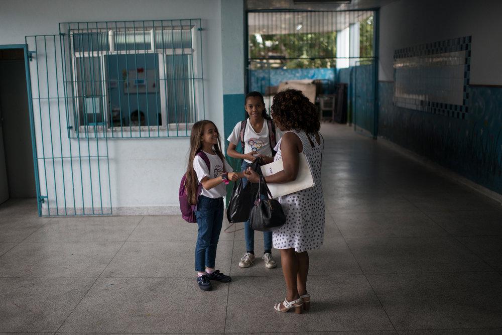 Dez. 7, 2017. Depois das primeiras funções matutinas, Sarah vai às escolas onde dá aula e ensaia. Na foto, a professora é presenteada por uma aluna ao chegar em uma escola da periferia da cidade para ensaiar o Coro Infanto-Juvenil.