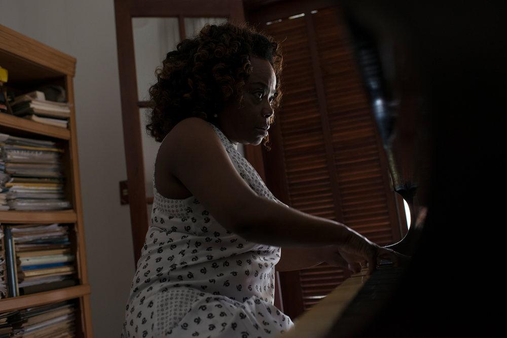 Dez. 7, 2017. Em casa, a pianista ensaia em seu piano tcheco. Como Volta Redonda, Sarah viu sua vida de desenvolver ao redor da CSN. Foi lá que seu pai trabalhou e prosperou, foi lá que alguns dos seus irmãos trabalharam e seria lá que ela trabalharia em algum momento da vida se não tivesse se encontrado na música. Ela viu no projeto Volta Redonda Cidade da Música a chance de ampliar o horizonte dos jovens volta-redondenses que, assim como Sarah, não viam seus futuros atrelados à CSN -- resistindo ao caminho habitual.