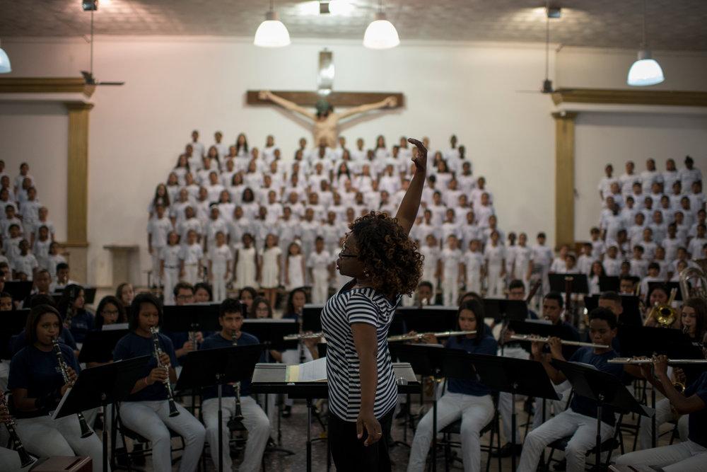 Dez. 6, 2017. Duas horas antes do concerto, Sarah ensaia com as crianças do Coro Infanto-Juvenil e da orquestra (foto). A maestrina faz uma média onde 50% dos alunos que participam do projeto se tornam músicos profissionais.