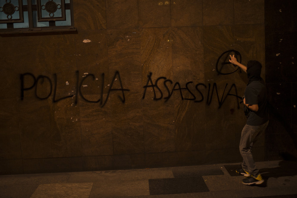 """March, 16, 2018. 7:30pm. A person writes """" police kill """" in a building in downtown Rio."""