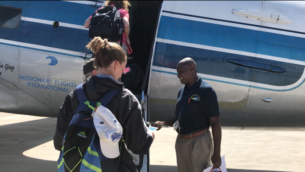Pastor Saintil greets passengers as they board an MFI plane at the Cap-Haitien airport.