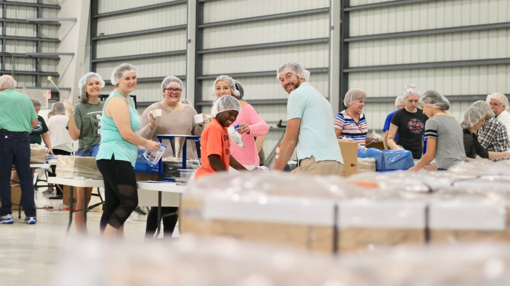 A group of friends works together to complete Manna Pack bags at the FMSC MobilePack™