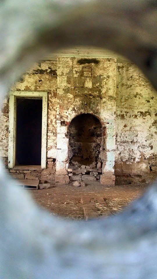 View of inside one of the locked buildings through a hole in the door.