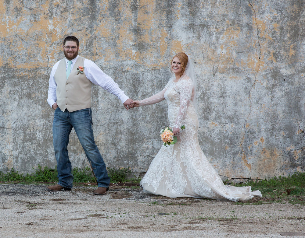 Bride and Groom at white wall