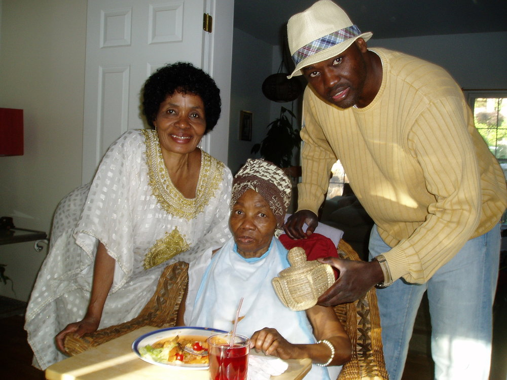 On July 4, 2009, I give my aunt, Phoebe, a birthday gift as her sister -- my mom -- smiles approvingly. The get-together occurs at North White Plains, New York, where Auntie Phoebe lives with her daughter, Dr. Kafui Demasio.