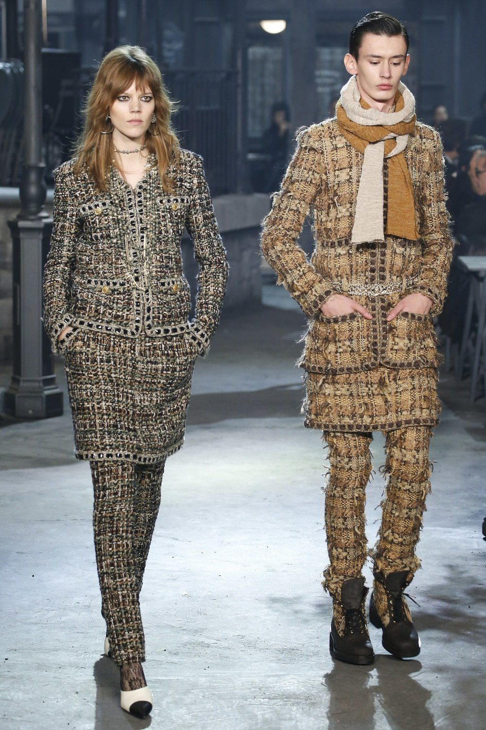 Models walk down the runway in tweed clothing from the Chanel Pre Fall 2016 collection.