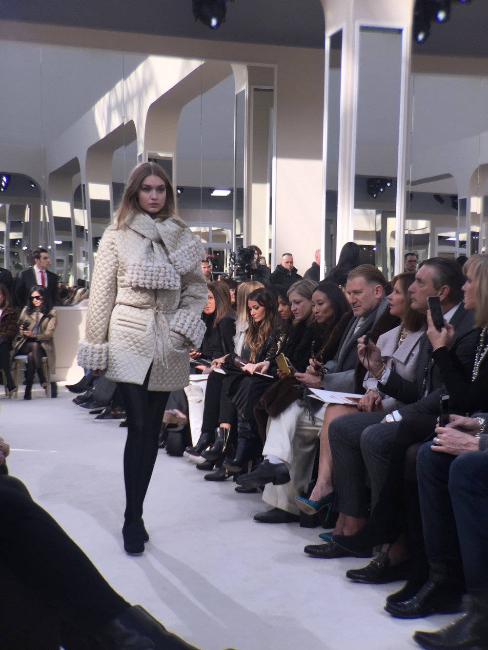 Gigi Hadid in a quilted beige coat and black tights