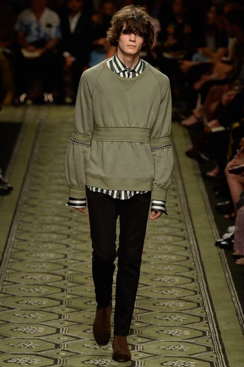 A male model walks down the runway in a sweatshirt from the Burberry Fall 2016 Ready to Wear Collection.