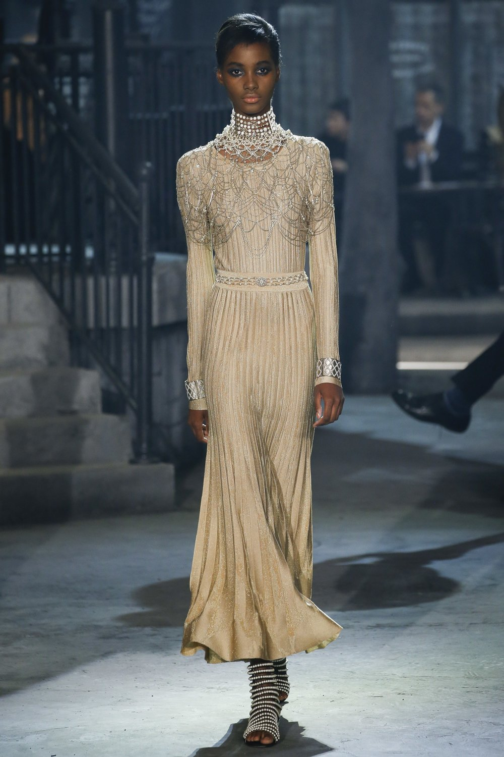 A model on the runway wearing a beautiful Chanel dress.