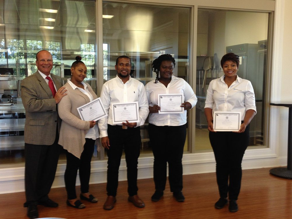 Vince Chelena, CAHA Executive Director, with recent graduates from the CPCC housekeeping training program.