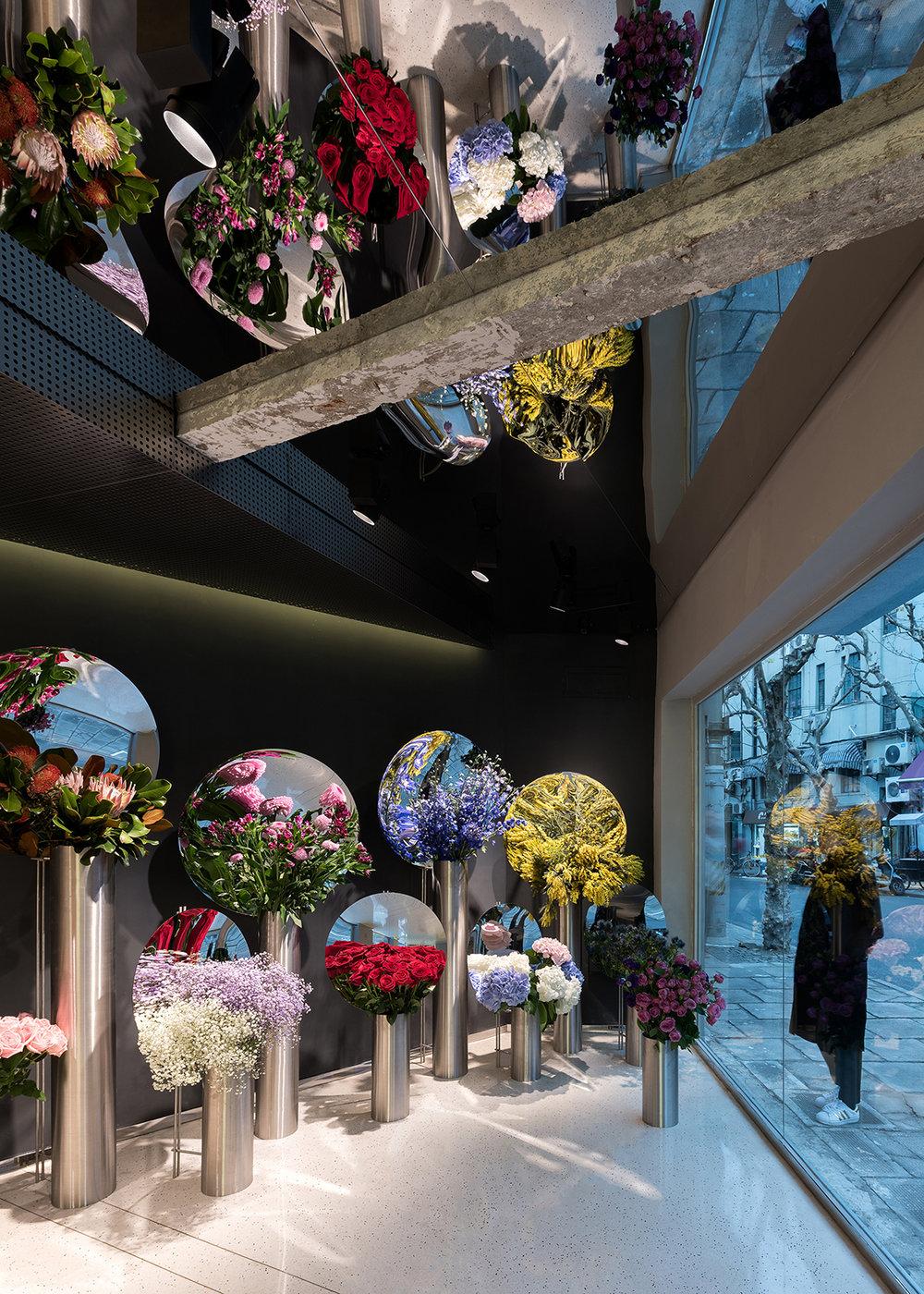 A  July's Flower,  em Xangai, projetada por Alberto Caiola usa espaços amplos, espelhos, metal escovado e concreto para criar um ambiente elegante onde as flores ganham destaque e se multiplicam.