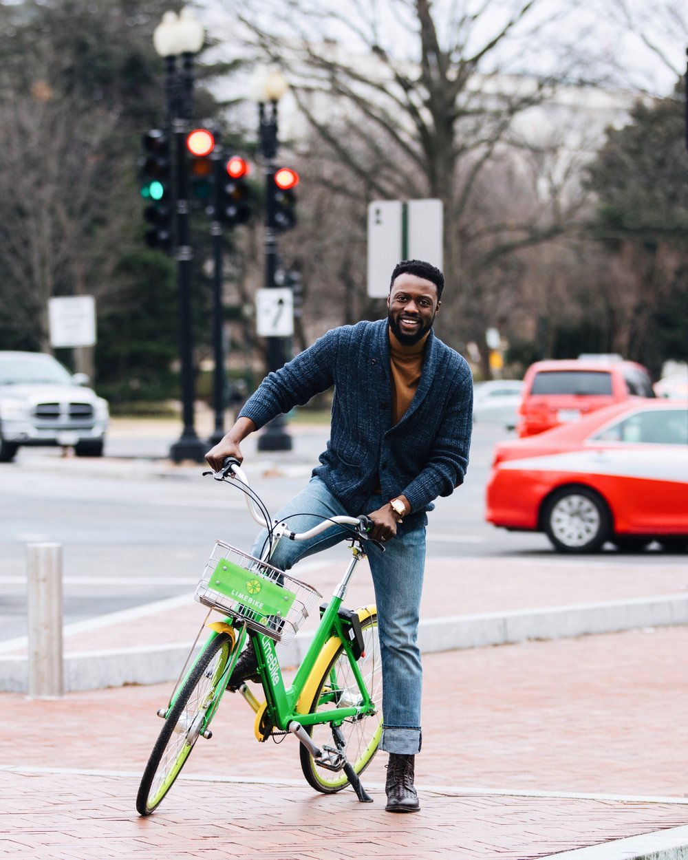 The Creative Gentleman riding  green Limebike in Washington, D.C. The Creative Gentleman was wearing blue J. Crew jeans, navy J. Crew cardigan with brown suede elbow patches, camel colored turtleneck, and brown leather watch. This image was taking for the Limebike Lime Nation campaign.