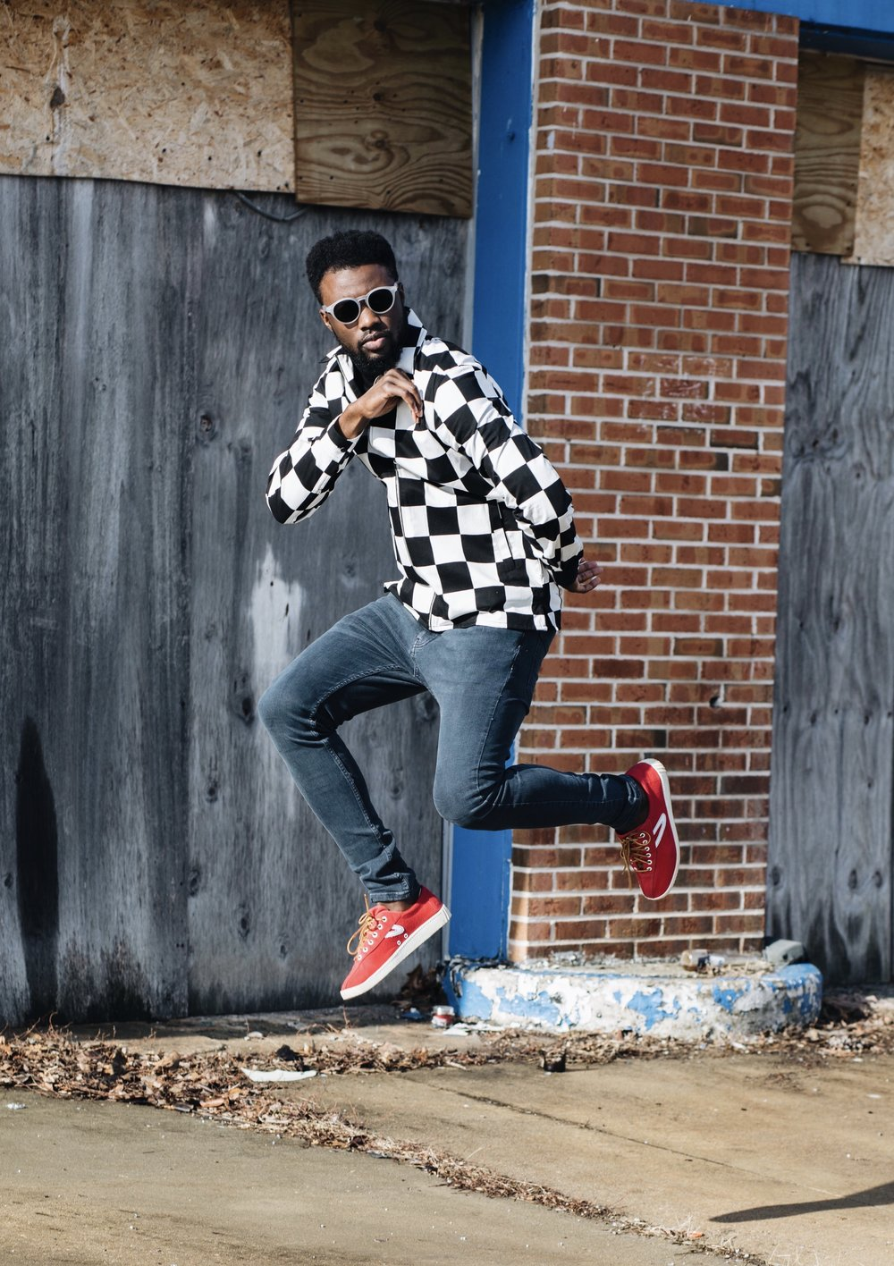 The Creative Gentleman is wearing blue Topman jeans, Topman black and white checkered shirt, red Tretorn Nylite sneakers, and sunglasses. The Creative Gentleman created this image as part of collaboration with Topman for their celebration of  being the destination for denim.