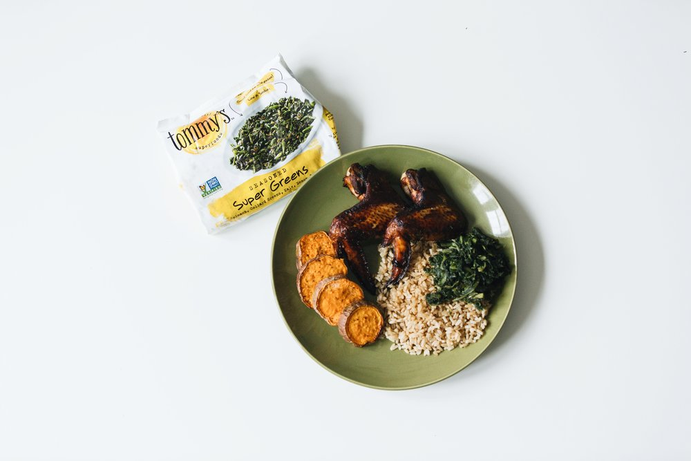 A green plate with sweet potatoes, chicken wings, brown rice, and Tommy's Superfoods Seasoned Super Green veggies. The Creative Gentleman created this image as part of Tommy's Superfoods think veggies first campaign.