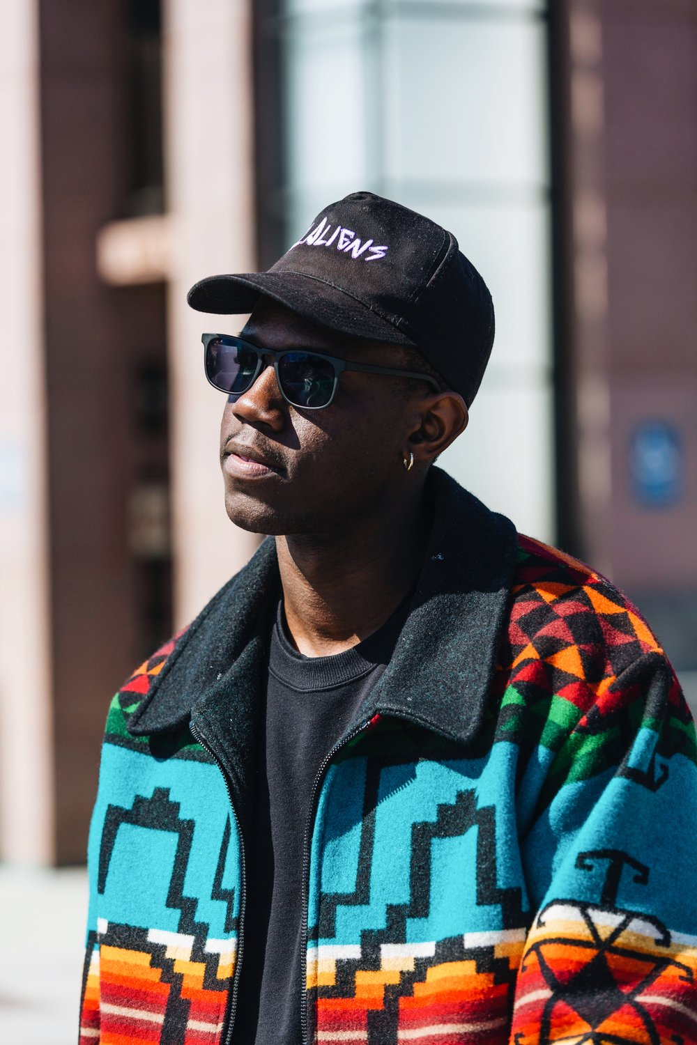 Image of DC creative 1takeace wearing black hat with white words, black sweatshirt, black sunglasses, and multicolored patterned jacket captured by photographer The Creative Gentleman during Walk with Locals two year anniversary walk.