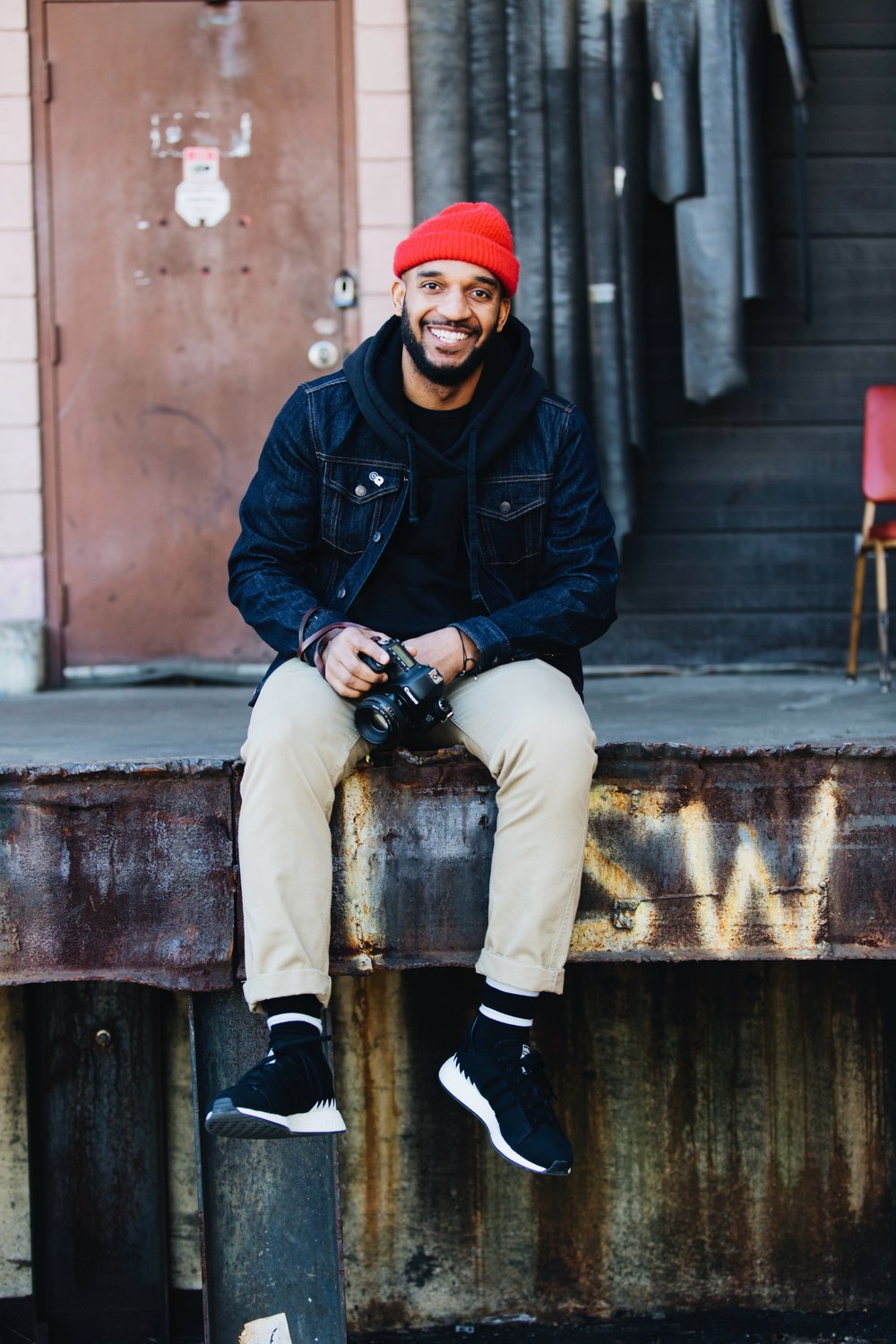 Photograph of photographer Master Williams wearing red beanie hat, black hoodie, blue jean jacket, tan chinos, striped socks, and a pair of Adidas sneakers captured by photographer The Creative Gentleman following the Walk with Locals two year anniversary walk.
