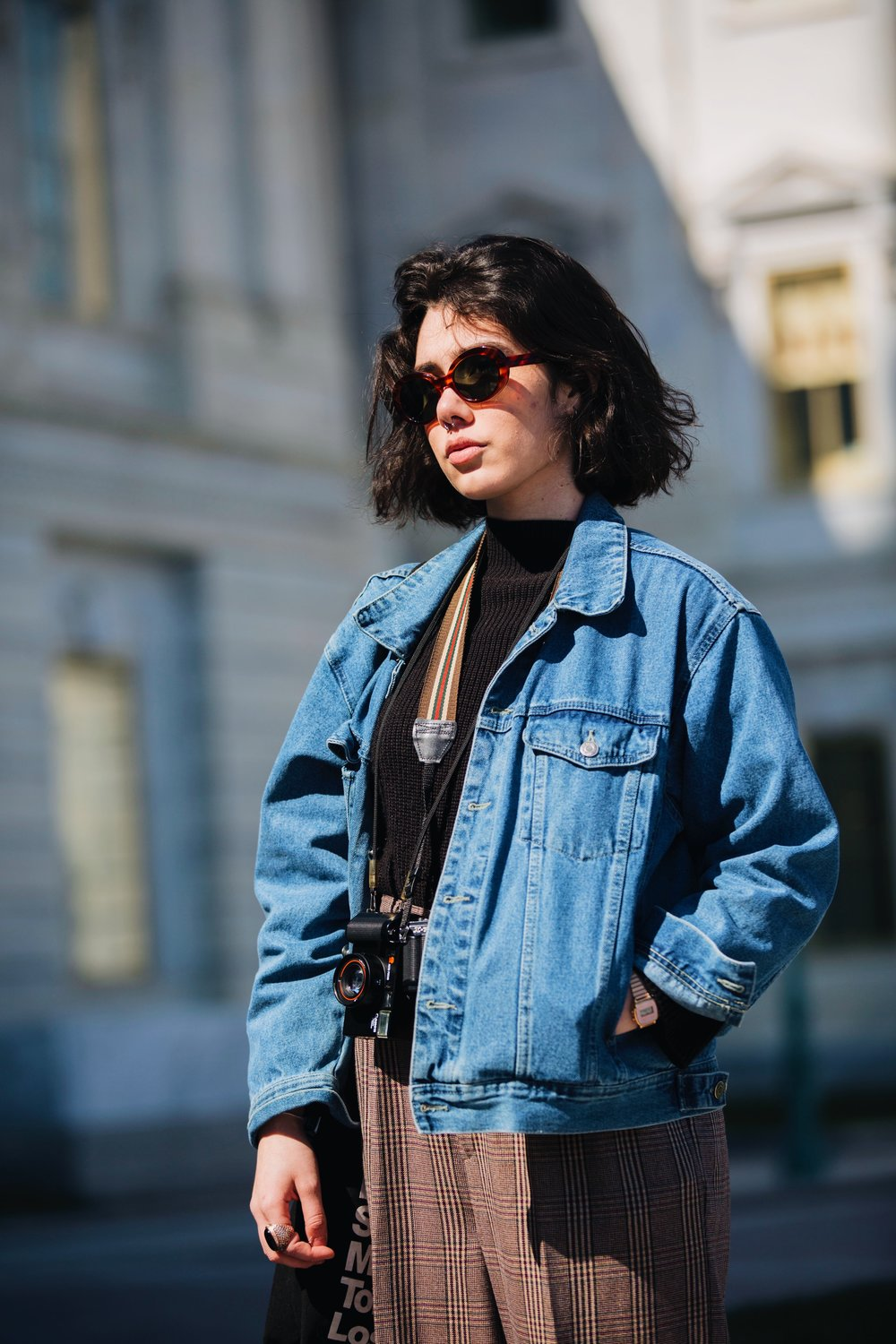 Photograph of photographer Ingridi Viruel wearing blue jeans jacket, glen plaid trouser, sunglasses, black sweater,and a film camera captured by photographer The Creative Gentleman during the Walk with Locals two year anniversary walk.