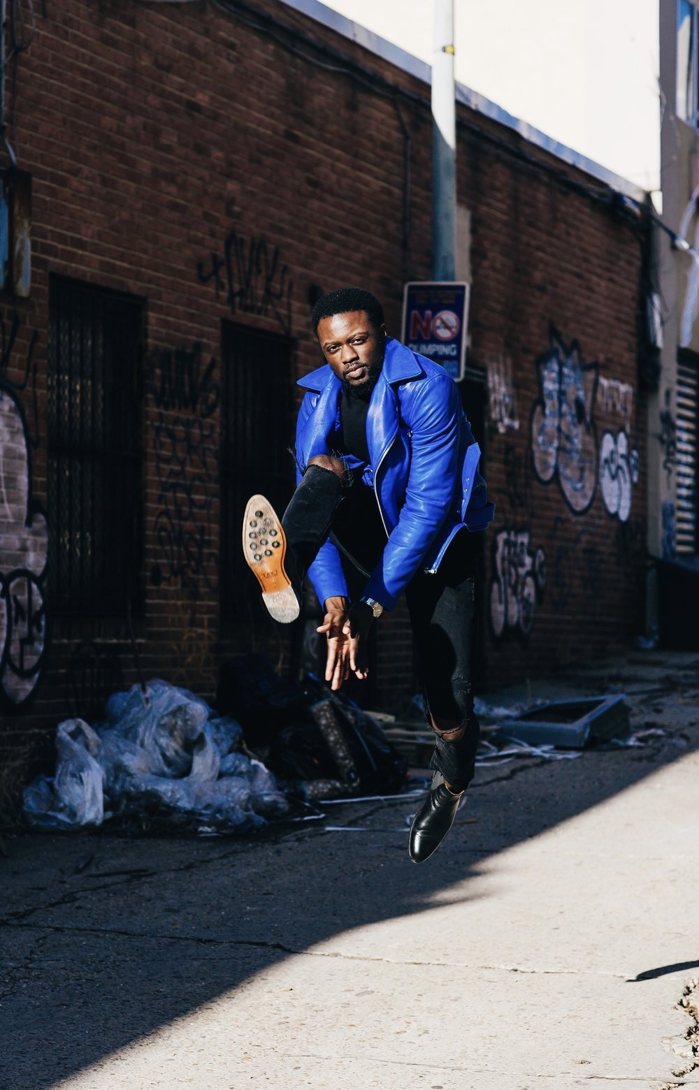 Brand influencer the creative gentleman wearing, royal blue leather jacket, black ripped jeans, and black Chelsea boots from Taft. He is jumping in the air clapping his hands between his legs.