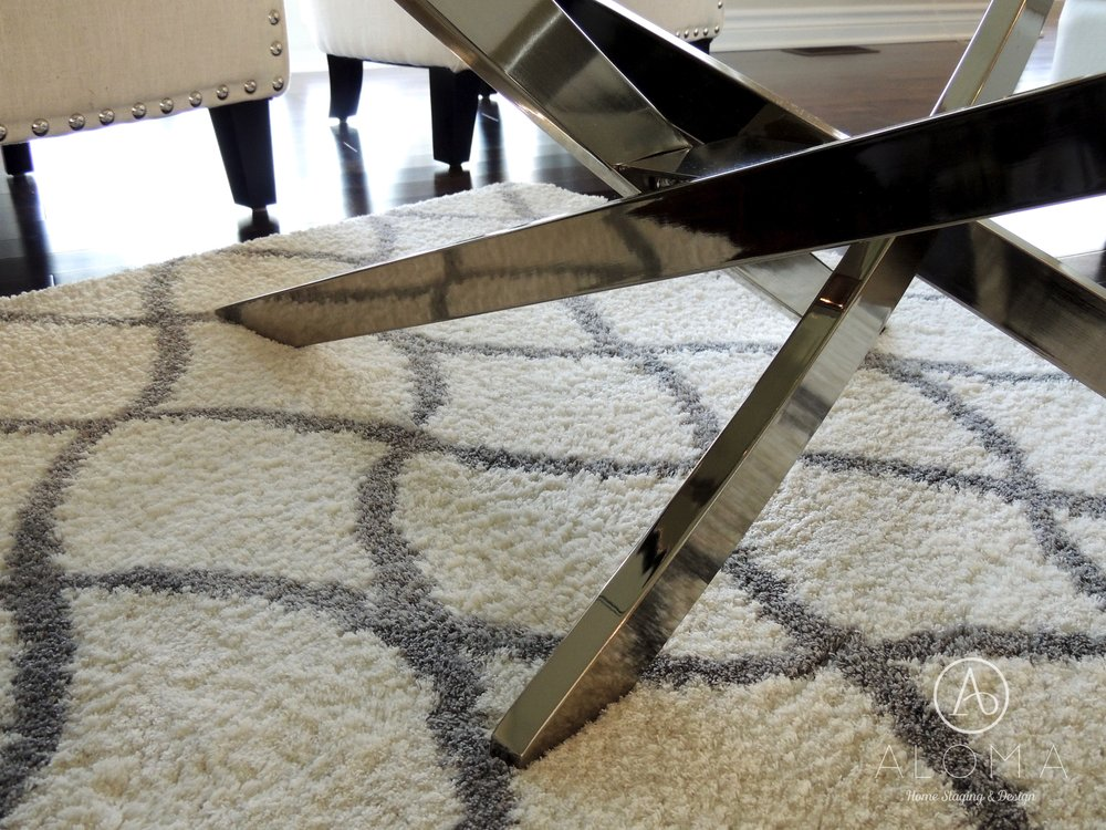 White area rug with grey trellis pattern and a contemporary coffee table with chrome legs