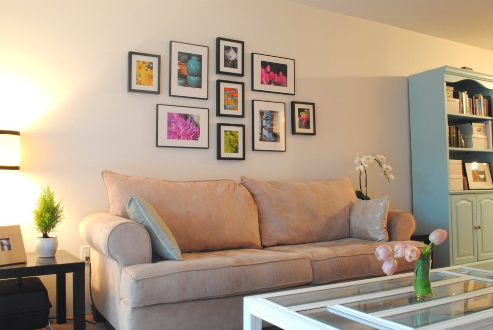 I love the color used in this arrangement. It's clear that's what this homeowner wanted to highlight. The arrangement and spacing is great, but the scale of the frames feels too small for the size of the sofa. The smaller photos would really pop if they were in frames with larger mats and would hold up a little better to the size of the wall and the surrounding pieces. Mixed sizes are fine and often really interesting, but in this case, bigger would be better.