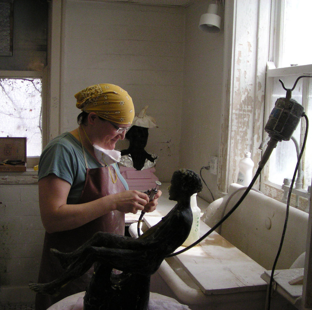 Melanie Hunter cold-working a nearly opaque glass piece in the studio.