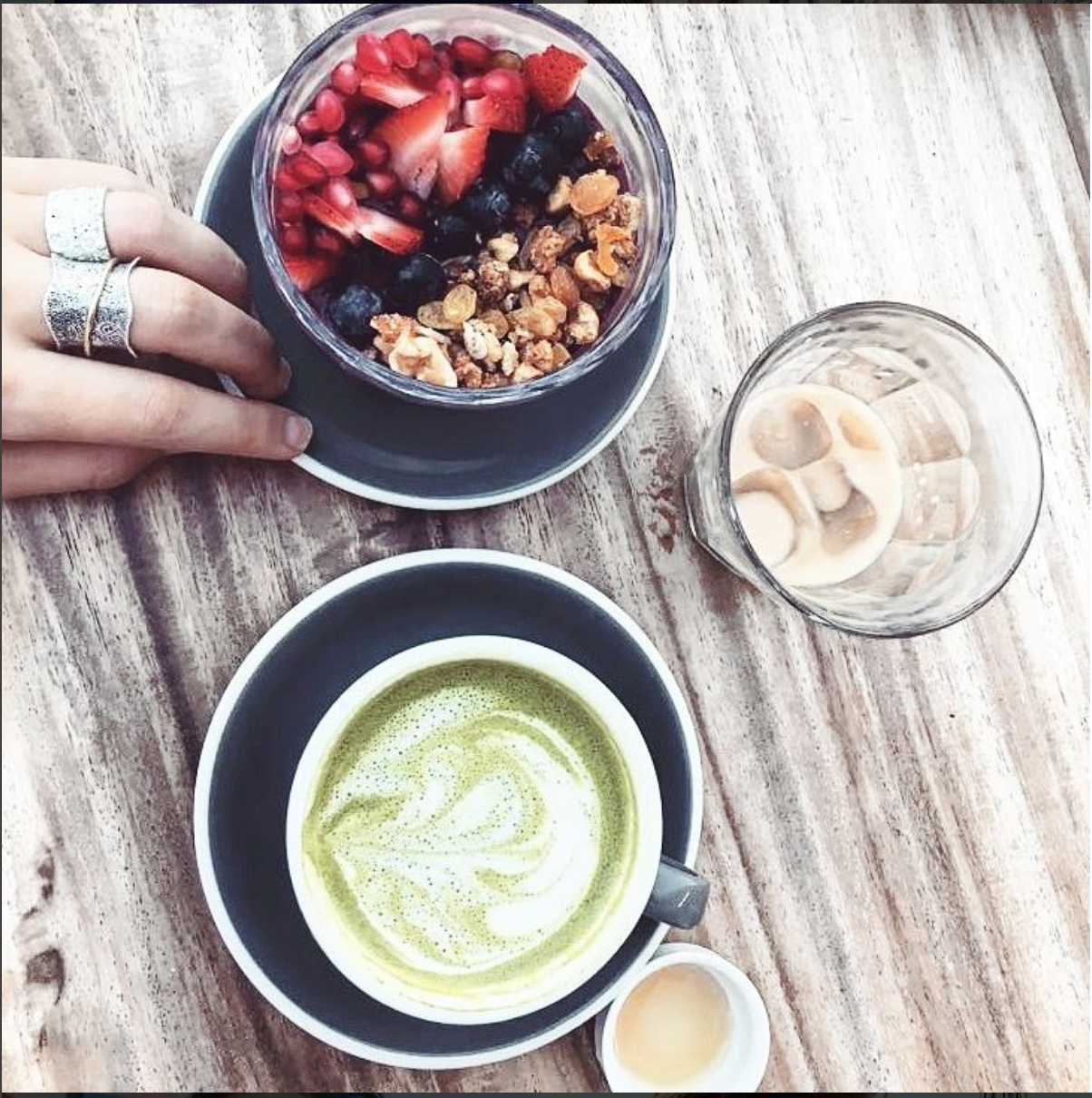 matcha latte, soy iced coffee and Stomping Grounds Dubai acai bowl with strawberries, fruit and granola on minimalist wooden background