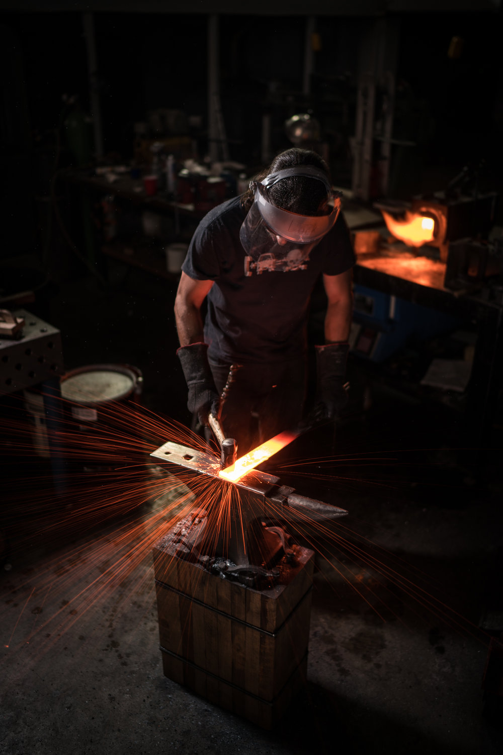 Here, Lock is striking a piece of damascus steel in the early stages of forging.