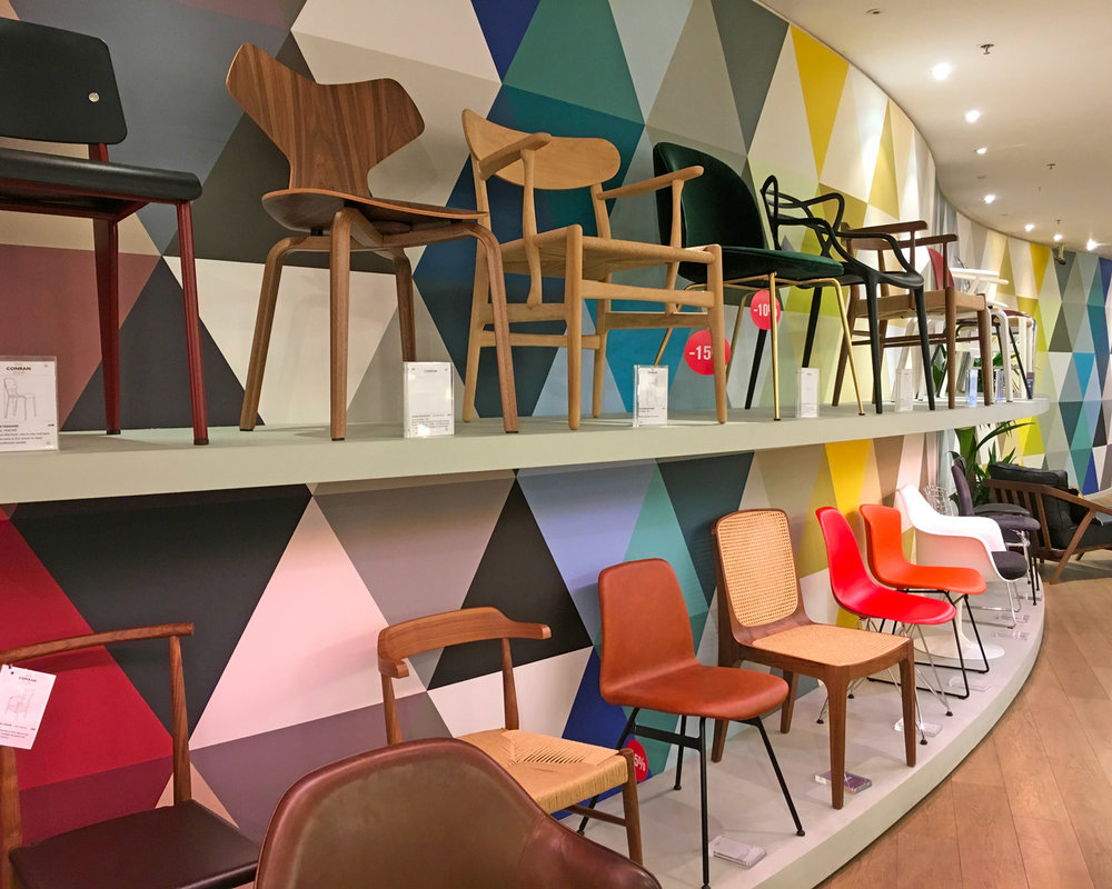 Various chairs at Conran Shop on display along an undulating, color-charged wall.
