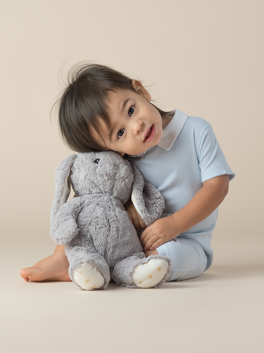 studio portrait of a baby boy snuggling a stuffed bunny