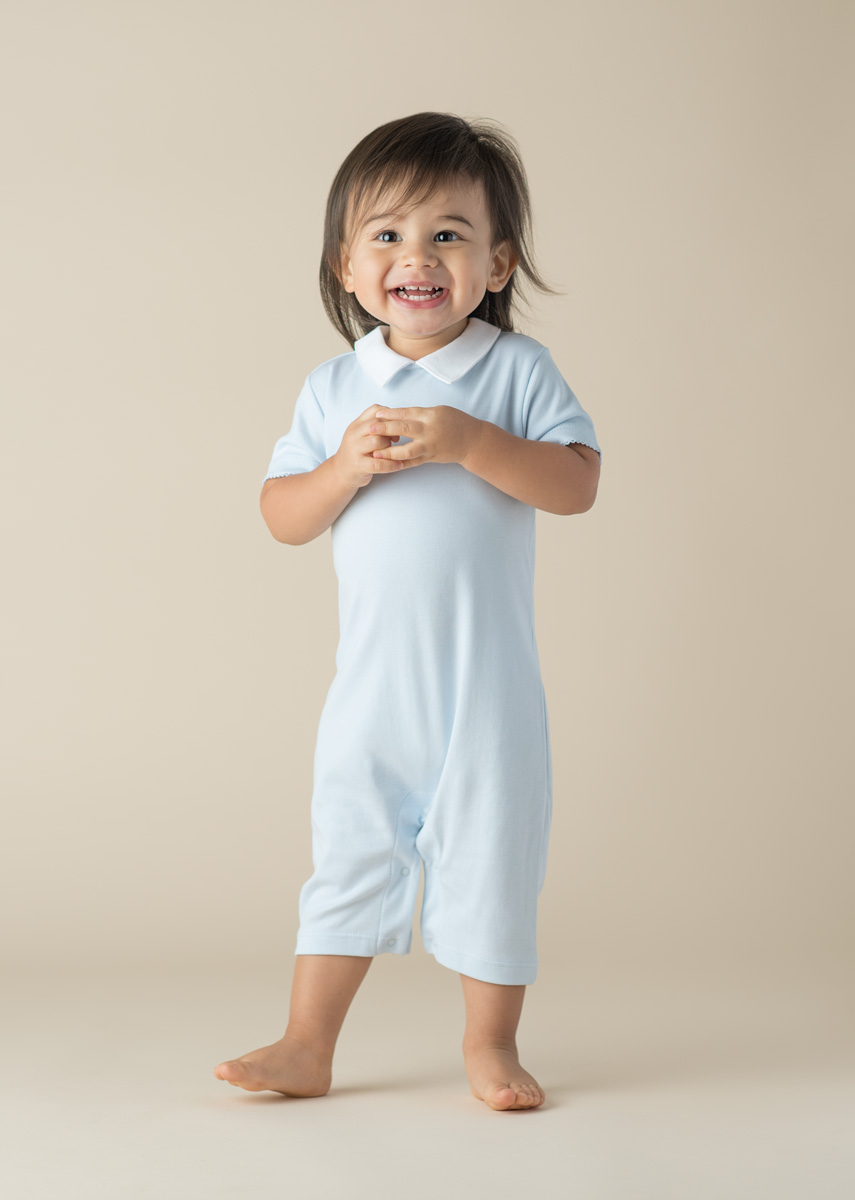 studio portrait of a baby boy wearing blue Dondolo outfit