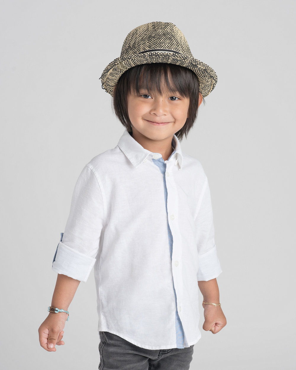 studio portrait of a young boy in a fedora
