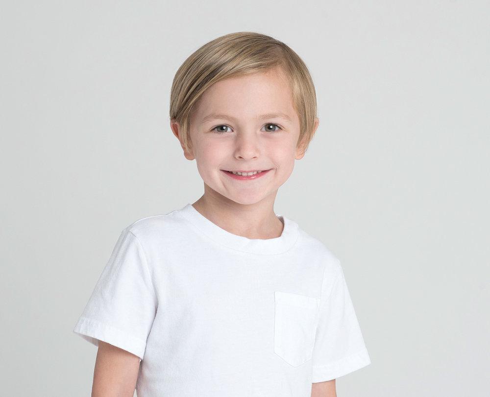 studio portrait of a boy wearing a white shirt