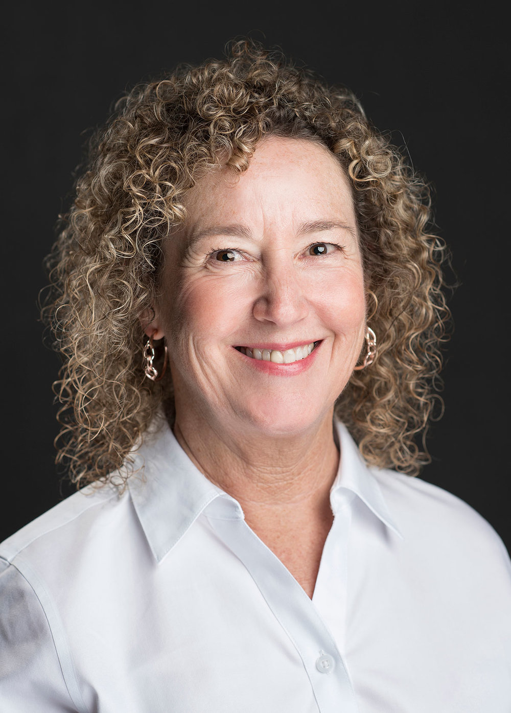 Professional headhshot of woman with curly hair